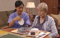 Health care provider assiting a patient with eating a meal